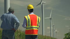 Farmer and engineer looking at windmills, cornfields Stock Footage