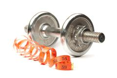 dumbbell and measuring tape - stock photo