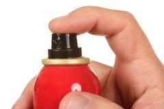 Red spray bottle in his hand Stock Photos