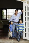 Hispanic father and sons in doorway - stock photo