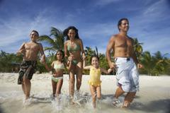 Hispanic family running into water Stock Photos