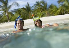 Hispanic couple with snorkeling gear in water Stock Photos
