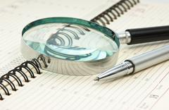 pen and magnifying glass - stock photo