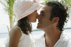 Stock Photo of Hispanic girl kissing father on nose