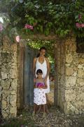 Hispanic mother and daughter in garden doorway Stock Photos