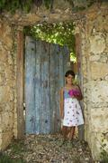 Hispanic girl standing in garden doorway - stock photo