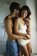 Stock Photo of Hispanic couple in underwear hugging
