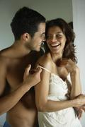 Hispanic man pulling down girlfriend's camisole strap Stock Photos