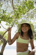Hispanic girl in bathing suit under tree Stock Photos