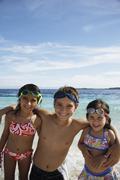 Hispanic siblings hugging at beach Stock Photos