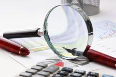 Magnifying glass and the working pape Stock Photos
