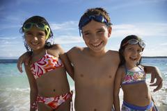 Hispanic siblings hugging at beach - stock photo