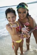 Stock Photo of Hispanic sisters holding starfish
