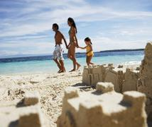 Hispanic family with sand castle in foreground Stock Photos