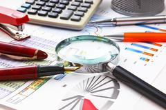 Magnifying glass and the working paper Stock Photos