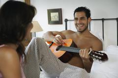 Hispanic man playing guitar for girlfriend Stock Photos