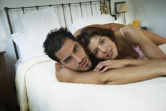 Hispanic couple hugging in bed Stock Photos