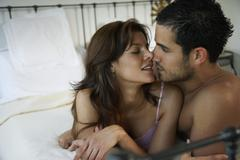 Hispanic couple kissing on bed Stock Photos