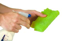 Hand with spray bottle and rag Stock Photos