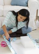 Pacific Islander woman wrapping gift - stock photo