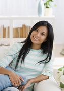 Pacific Islander woman sitting on sofa - stock photo