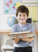 Hispanic boy holding stack of school books Stock Photos