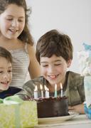 Hispanic boy looking at birthday cake Stock Photos