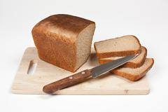 sliced rye bread and knife - stock photo