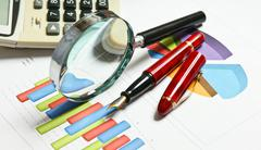 magnifying glass and the working paper - stock photo