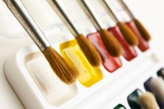 Watercolor paints and  brushes Stock Photos