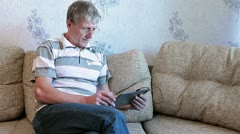 Mature adult sitting with pad on divan - stock footage