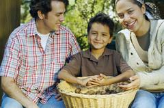 Stock Photo of Multi-ethnic family with basket of organic produce