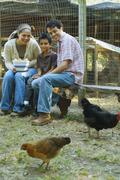 Multi-ethnic family holding bowl of eggs next to chickens - stock photo