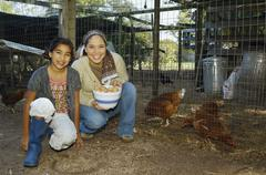 Hispanic mother and daughter with bowl of eggs next to chickens - stock photo