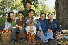 Multi-ethnic family sitting under tree Stock Photos