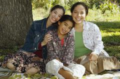 Multi-ethnic family sitting under tree Stock Photos