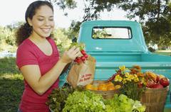 Hispanic women at organic farm stand Stock Photos