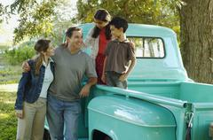 Stock Photo of Multi-ethnic family in back of truck