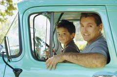 Stock Photo of Hispanic father and son sitting in truck