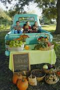 Multi-ethnic family in truck at farm stand Stock Photos