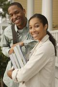 African couple carrying books and backpack Stock Photos