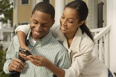 African couple looking at cell phone Stock Photos