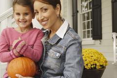 Stock Photo of Hispanic mother and daughter holding pumpkin