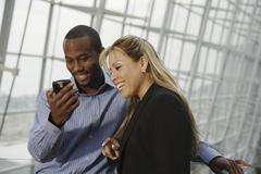 Stock Photo of Multi-ethnic businesspeople looking at cell phone