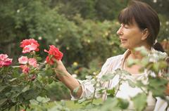 Senior Hispanic woman looking at rose - stock photo