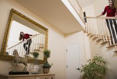 Hispanic woman looking in mirror from stairs Stock Photos