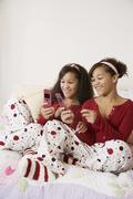 Stock Photo of African twin sisters looking at cell phones
