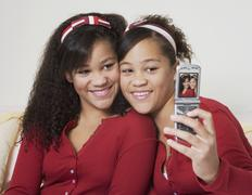 Stock Photo of African twin sisters taking own photograph