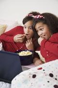 African twin sisters watching movie Stock Photos