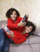 Stock Photo of African twin sisters playing video games